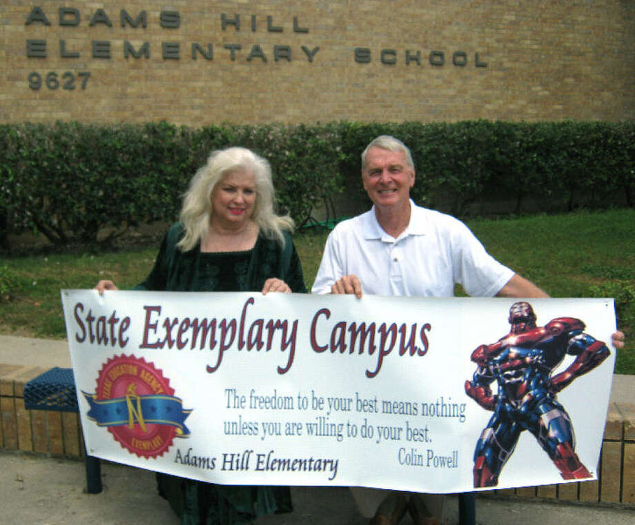 In better times, Vice Principal Karon Wernli and Principal Donald Powers hold a sign at Adams Hill Elementary School. Wernli, Powers and a reading specialist were placed on leave. Photo: Courtesy Photo