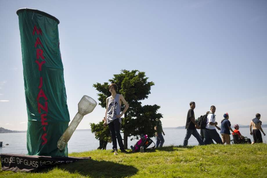 Skiler Dewitz, of Mary Jane's House of Glass, center, talks to his friend, left, encased in a 12-foot cloth bong costume on the first day of Seattle Hempfest Friday, August 16, 2013, at Myrtle Edwards Park in Seattle. The annual event, which advocates the idea of decriminalized marijuana, continues through Sunday. Photo: JORDAN STEAD, SEATTLEPI.COM