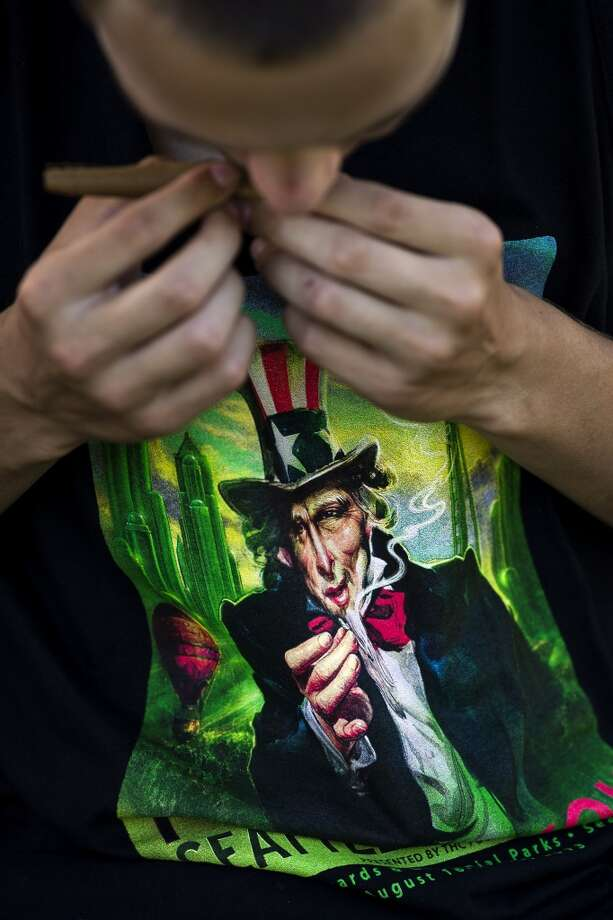 Uncle Sam appears to offer up a joint on a young man's T-shirt under a blunt-in-the-making on the first day of Seattle Hempfest Friday, August 16, 2013, at Myrtle Edwards Park in Seattle. The annual event, which advocates the idea of decriminalized marijuana, continues through Sunday. Photo: JORDAN STEAD, SEATTLEPI.COM