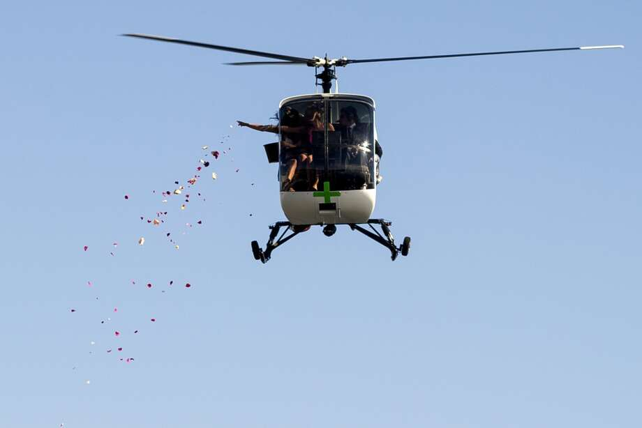 A low-flying helicopter hovers near the waterfront as the passenger throws what appears to be flower petals downward on the first day of Seattle Hempfest Friday, August 16, 2013, at Myrtle Edwards Park in Seattle. The annual event, which advocates the idea of decriminalized marijuana, continues through Sunday. Photo: JORDAN STEAD, SEATTLEPI.COM
