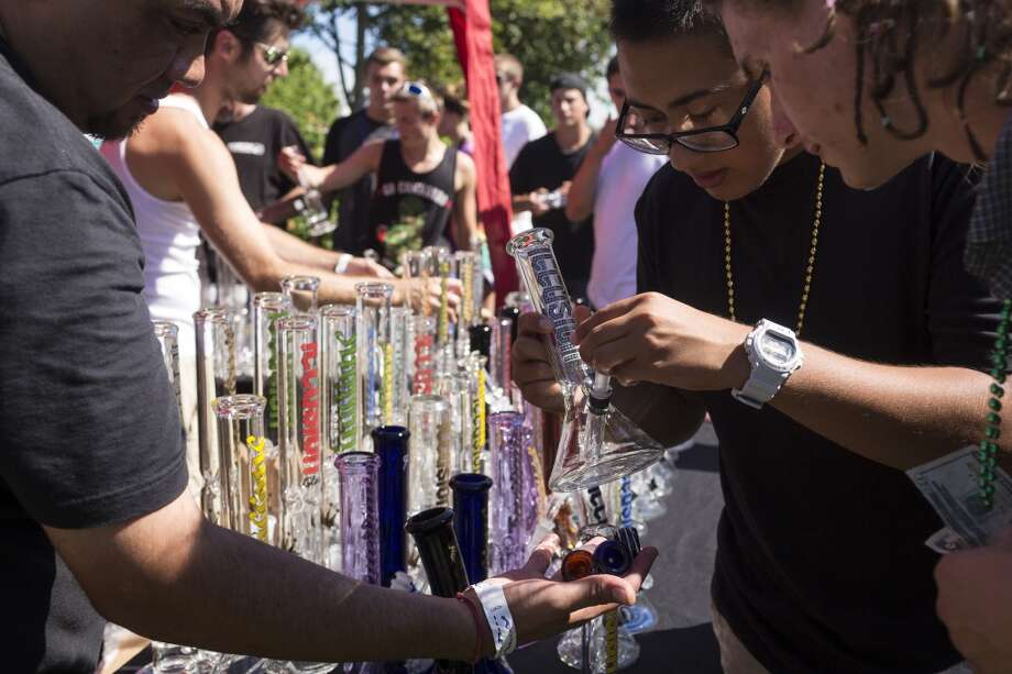 Onlookers examine glass Illusion bongs on the first day of Seattle Hempfest Friday, August 16, 2013, at Myrtle Edwards Park in Seattle. The annual event, which advocates the idea of decriminalized marijuana, continues through Sunday. Photo: JORDAN STEAD, SEATTLEPI.COM