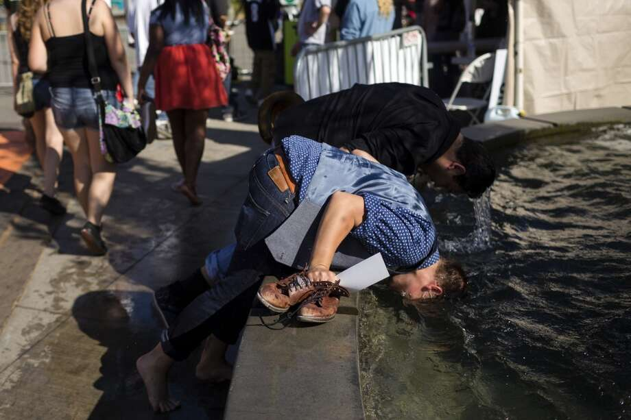 To avoid the heat, event attendees dunk their heads in a nearby fountain on the waterfront on the first day of Seattle Hempfest Friday, August 16, 2013, at Myrtle Edwards Park in Seattle. The annual event, which advocates the idea of decriminalized marijuana, continues through Sunday. Photo: JORDAN STEAD, SEATTLEPI.COM