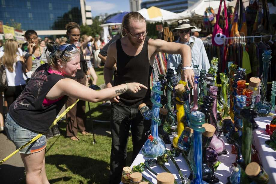 An onlooker examines bongs for purchase on the first day of Seattle Hempfest Friday, August 16, 2013, at Myrtle Edwards Park in Seattle. The annual event, which advocates the idea of decriminalized marijuana, continues through Sunday. Photo: JORDAN STEAD, SEATTLEPI.COM