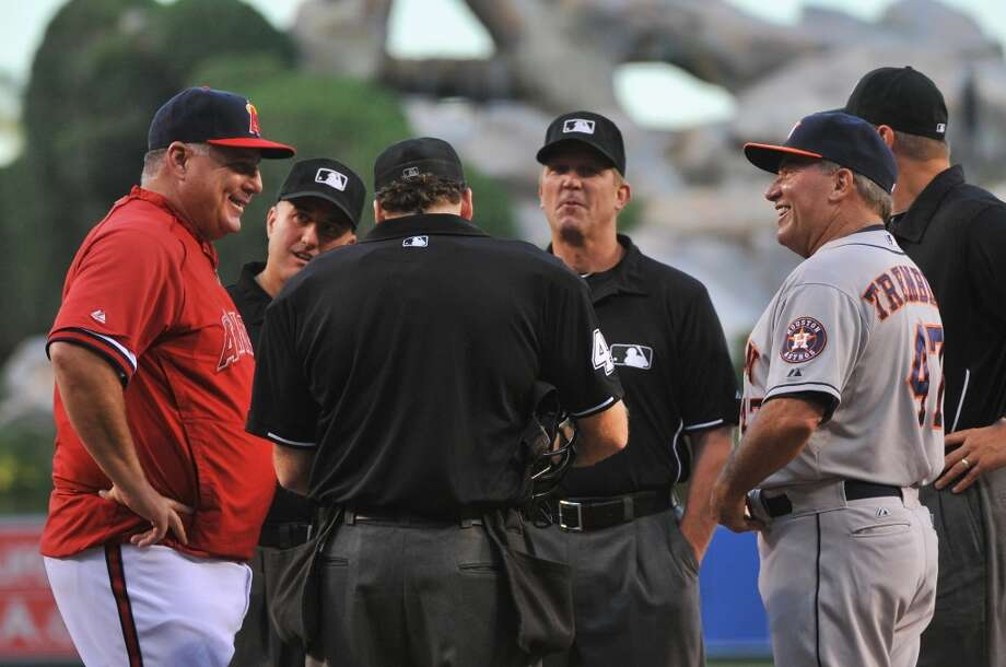 Angels manager Mike Scioscia and Astros third base coach Dave Trembley talk with the umpires before the first game of the series. Photo: Jonathan Moore, Getty Images