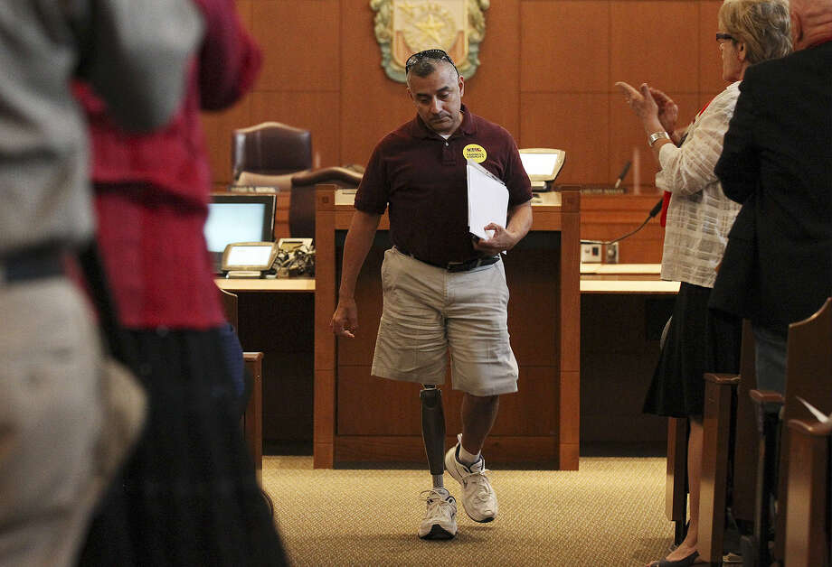 Decorated Iraq veteran Eric Alva leaves the dais after speaking in favor of changes to the city's anti-bias policy. Photo: Kin Man Hui / San Antonio Express-News