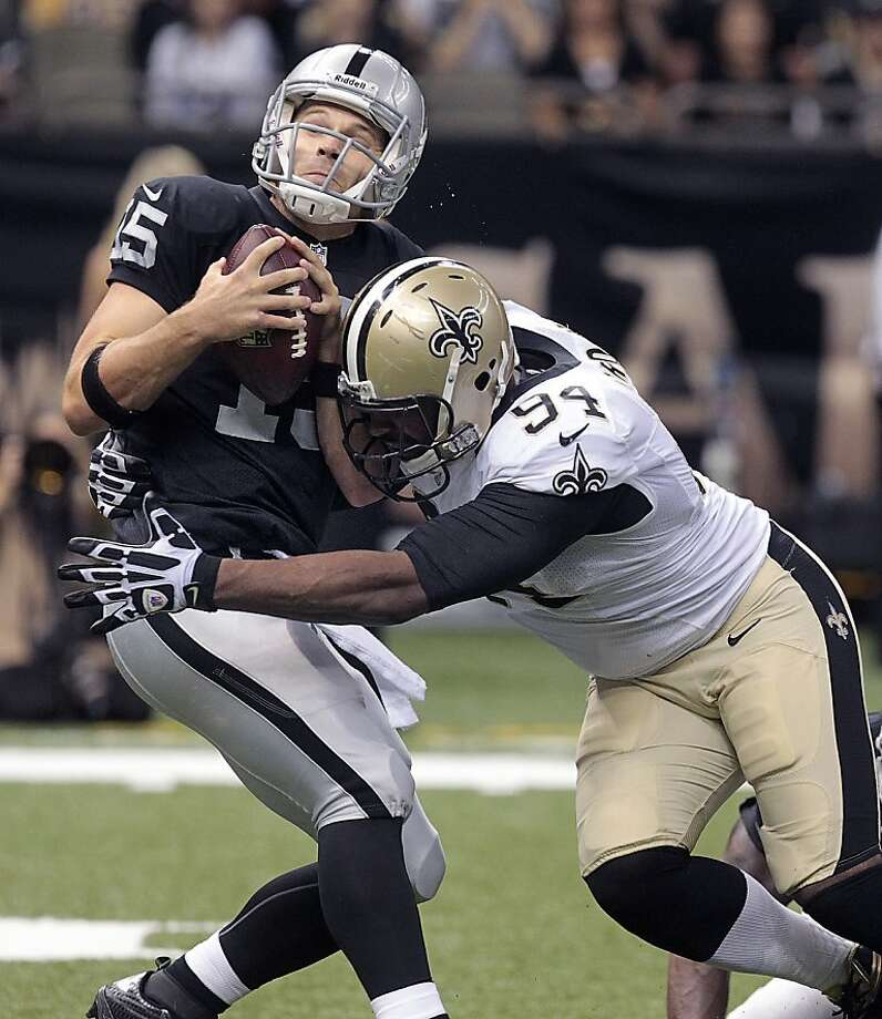 Matt Flynn sustains one of five sacks, this one by the Saints' Cameron Jordan. Photo: Matthew Hinton, Associated Press