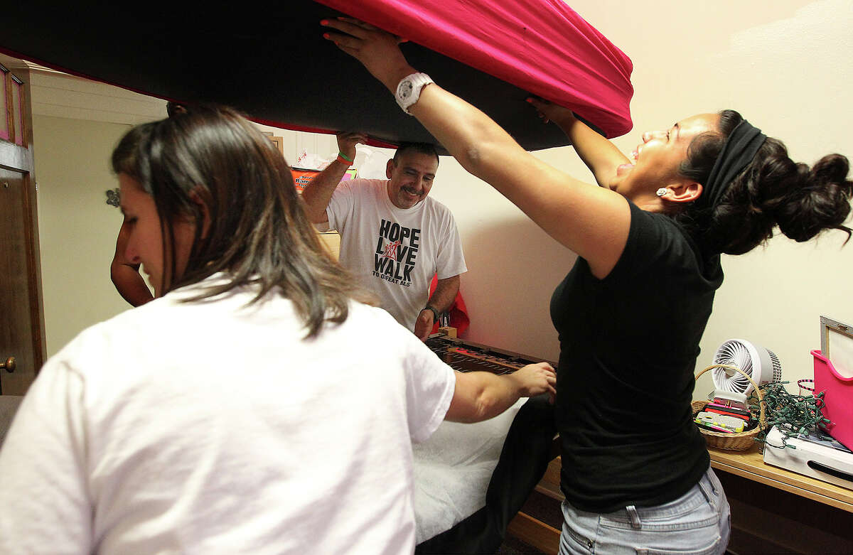 Mikaela Flores (right) laughs as her father, Sam, and others help arrange her dorm room at the University of Incarnate Word during freshman move-in day on Thursday, Aug. 15, 2013. Parents and freshman made a day of moving into the dorm rooms on campus for the upcoming semester.