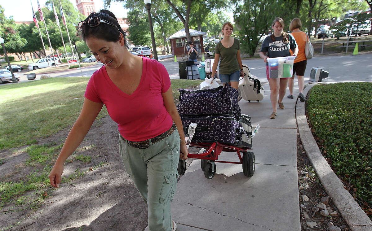 Magdeline Cook (left) uses a dolly to move her daughter, Elisabeth, into her dorm room at the University of Incarnate Word during freshman move-in day on Thursday, Aug. 15, 2013. Parents and freshman made a day of moving into the dorm rooms on campus for the upcoming semester.
