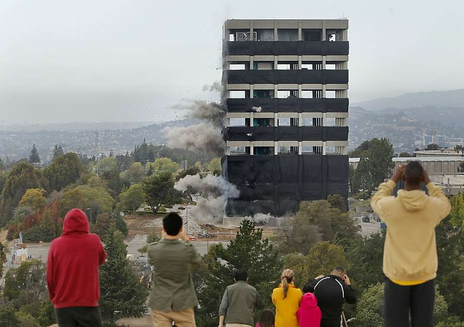 The initial charges are deployed as crowds gather on a nearby hillside to watch as the thirteen story tall Warren Hall building on the Cal State University East Bay campus is imploded in Hayward, Ca., Saturday August 17, 2013. Photo: Michael Macor, San Francisco Chronicle