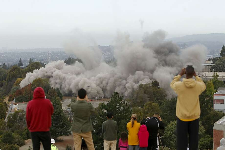 Dust rises as crowds gather on a nearby hillside to watch as the thirteen story tall Warren Hall building on the Cal State University East Bay campus is imploded in Hayward, Ca., Saturday August 17, 2013. Photo: Michael Macor, San Francisco Chronicle
