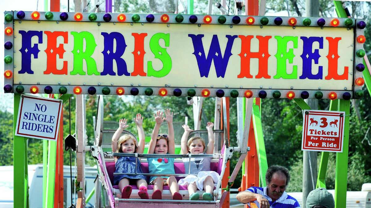 Twin sisters, Gemma Beecher, left, and Sophie, right, both 5, ride the ferris wheel with their sister Nella, 7, center, at the Bridgewater Country Fair in Bridgewater, Conn. Saturday, Aug. 17, 2013.