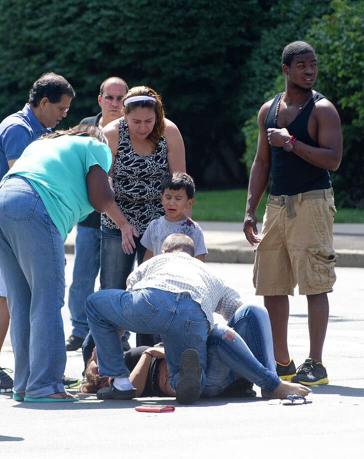 A woman and child are seen to by bystanders as they wait for emergency personnel at the intersection of East Main and Main Streets in Stamford, Conn., after they were hit by a green SUV on Saturday, August 17, 2013. Photo: Lindsay Perry / Stamford Advocate