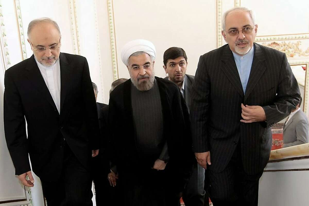 The new head of Iran's Atomic Energy Organization, Ali Akbar Salehi (left), and Foreign Minister Mohammad Javad Zarif flank President Hasan Rouhani en route to a Foreign Ministry handover.