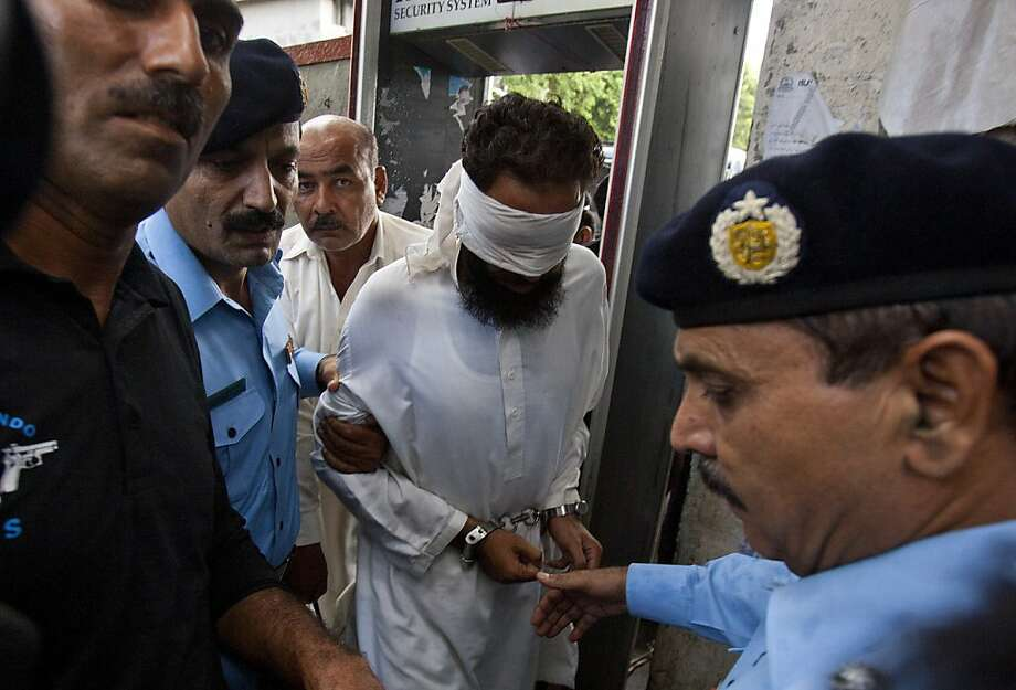 In this Sunday, Sept. 2, 2012, file photo, Pakistani police officers escort blindfolded Muslim cleric Khalid Chishti to appear in court in Islamabad, Pakistan. A lawyer says a Pakistani court has dismissed charges against the cleric who accused a young Christian girl of blasphemy and had been arrested for allegedly forging evidence against her. Photo: Anjum Naveed, Associated Press