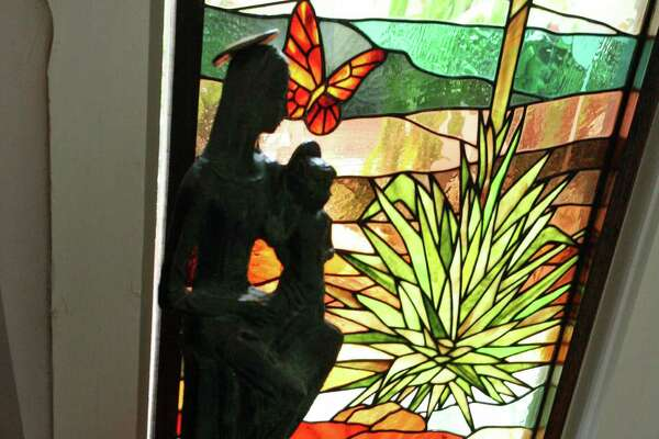A stained glass panel in a hallway window depicts a yucca plant.