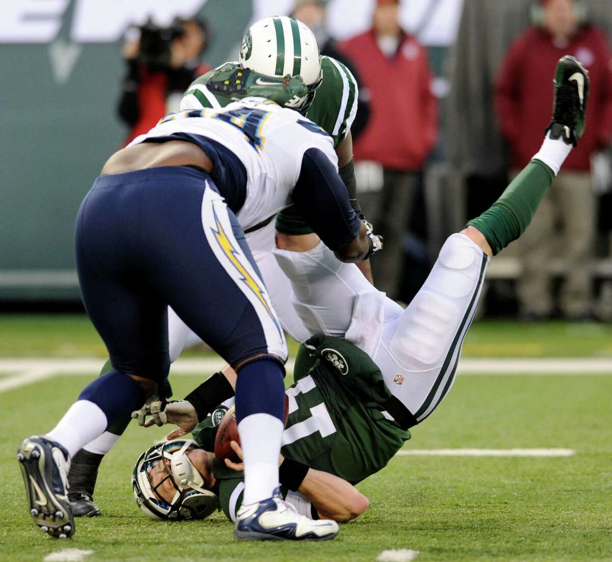 FILE - In this Dec. 23, 2012, file photo, New York Jets quarterback Greg McElroy, bottom, is sacked by San Diego Chargers defensive end Corey Liuget, front left, during the second half of an NFL football game in East Rutherford, N.J. McElroy, who was sacked 11 times last weekend, has a concussion and will be replaced by Mark Sanchez as the Jets' starting quarterback in the season finale at Buffalo on Sunday, coach Rex Ryan said. (AP Photo/Bill Kostroun, File)