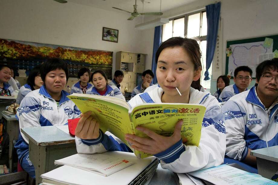 "Seventeen-year-old Chang Shui, center, or as she calls herself in English, ""Charlotte,"" sits with her school classmates in Shanghai, China. It was just a week after Chang Shui received her acceptance notice from Harvard that the first book offer came. A publisher approached her father with a detailed outline for an inside guide to how a Shanghai couple prepared their daughter to compete successfully with the best students from America. (Jonathan Browning/Los Angeles Times/MCT) Photo: Jonathan Browning, MBR / Los Angeles Times"