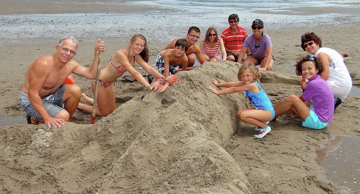 The Aults of Southport, Savianos of Southport and Derenches of Enfield collaborate to create a lobster at Fairfield PAL's Sand Sculpture Contest at Penfield Beach. FAIRFIELD CITIZEN, CT 8/17/13
