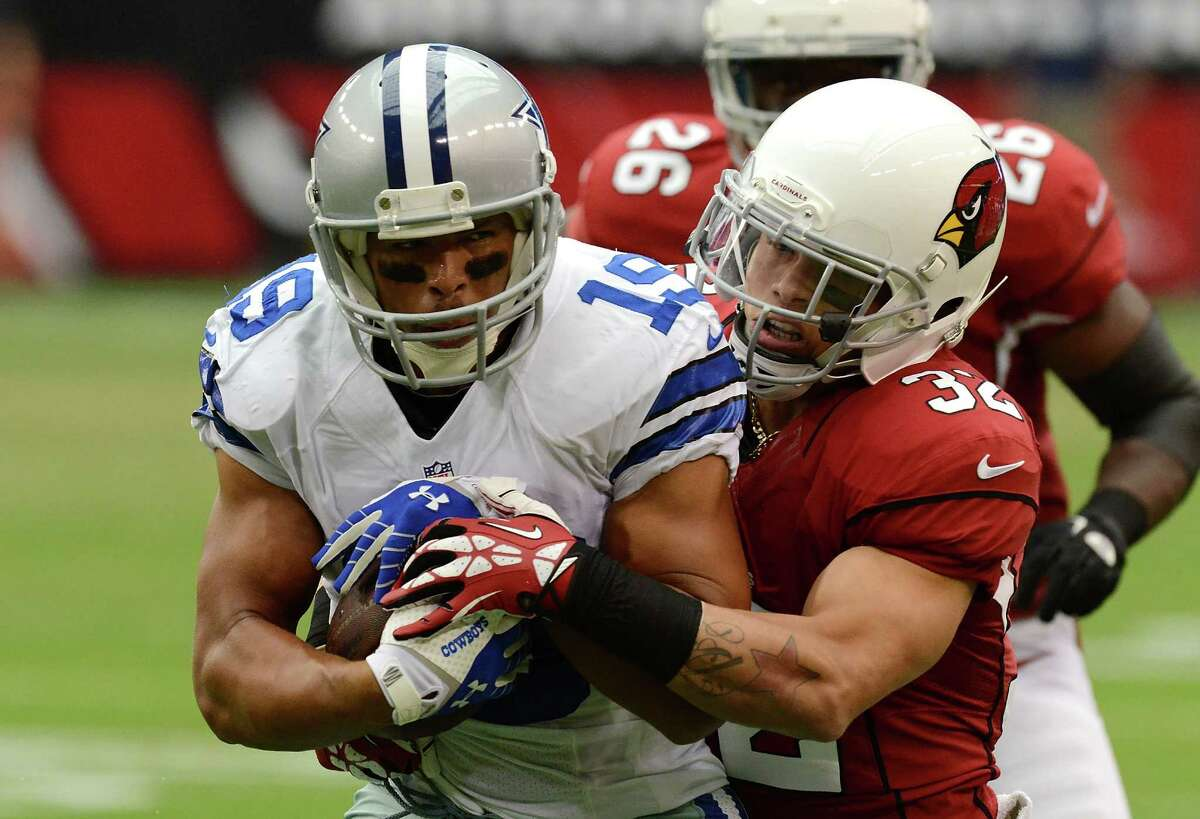 Miles Austin #19 of the Dallas Cowboys is tackled by Tyrann Mathieu #32 of the Arizona Cardinals at University of Phoenix Stadium on August 17, 2013 in Glendale, Arizona.