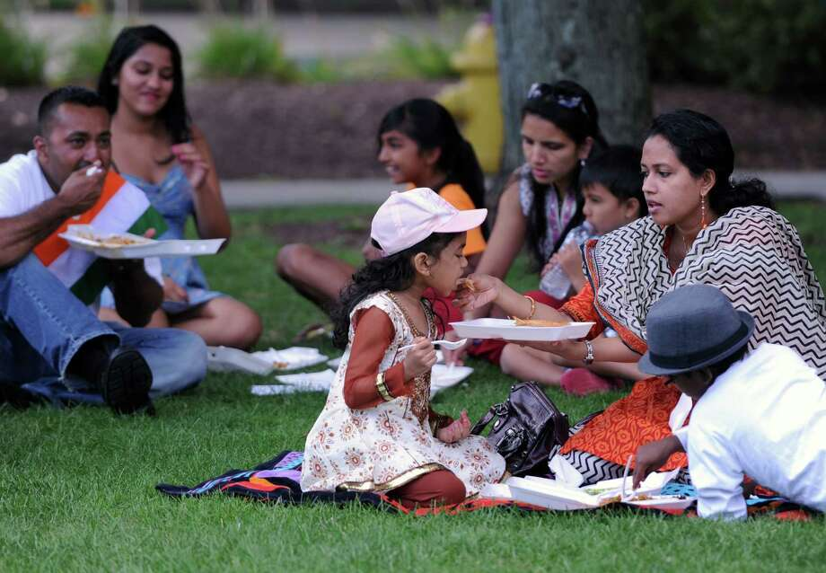 Izzah Nishad, 6, is fed a bite of Indian food by her mother Simi Nishad, of Danbury, at the Jai Ho Indian Festival at CityCenter Green in Danbury, Conn. on Saturday, Aug. 17, 2013.  The festival, presented by the Indian Association of Western CT, featured a variety of authentic Indian food, Indian clothing, art and children's activities.  Live karaoke during the day and a Bollywood concert with Rex D'Souza at night entertained festival-goers. Photo: Tyler Sizemore / The News-Times