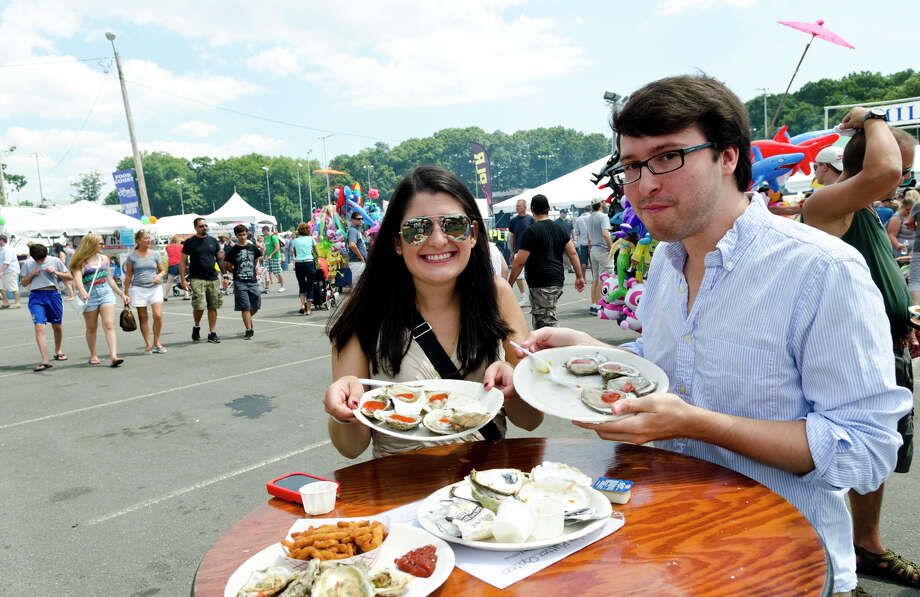 Caroline Walker and her husband, Marc, of New Haven, enjoy a plate of oysters during the 39th annual Milford Oyster Festival in downtown Milford on Saturday, Aug. 17, 2013. Photo: Amy Mortensen / Connecticut Post Freelance