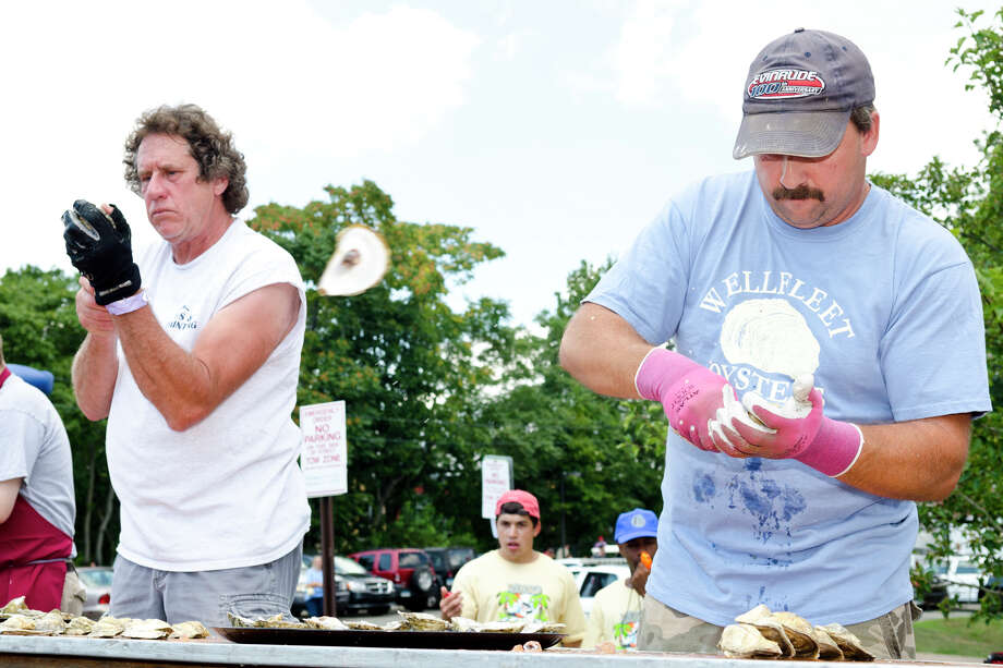 "Steve Trcka, of Milford, and William ""Chopper"" Young, of Wellfleet, compete during the first heat of the oyster shucking contest during the 39th annual Milford Oyster Festival in downtown Milford on Saturday, Aug. 17, 2013. Photo: Amy Mortensen / Connecticut Post Freelance"