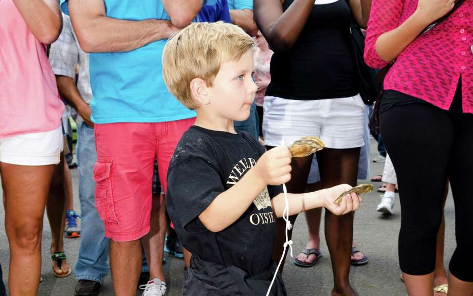 "Among a crowd of grownups, Eli Paine, 4, of Wellfleet, holds discarded oyster shells as he watches his father, William ""Chopper"" Young compete in the oyster shucking contest during the 39th annual Milford Oyster Festival in downtown Milford on Saturday, Aug. 17, 2013. Photo: Amy Mortensen / Connecticut Post Freelance"