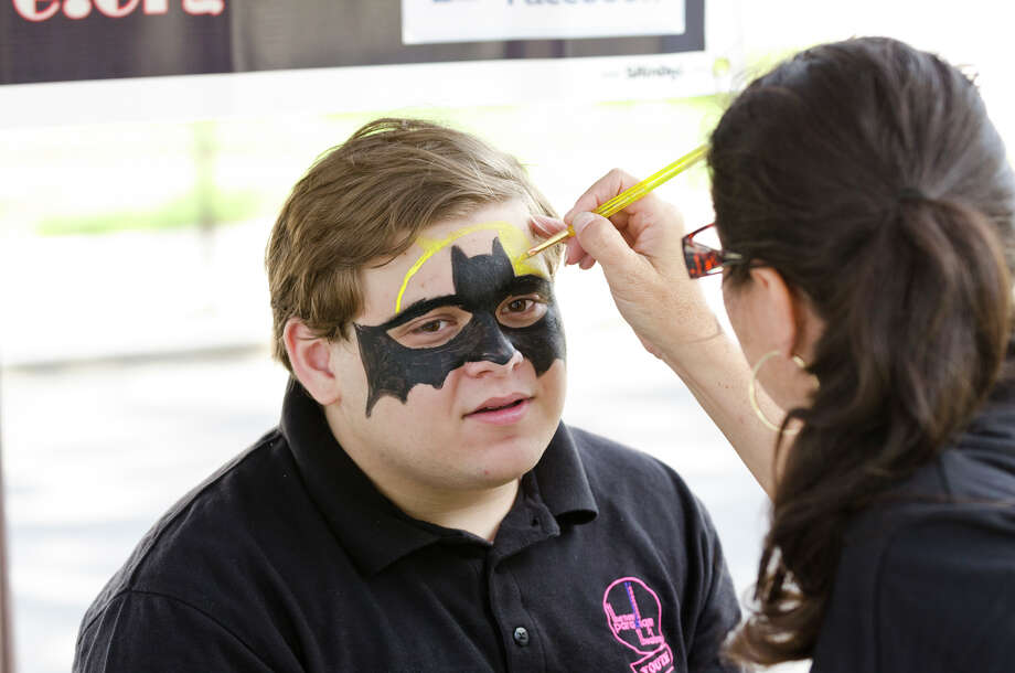 Lisa LaRusso, of the New Paradigm Theatre Company, paints Batman on the face of New Paradigm Theatre Company Youth Board member Nathan Clift, of Trumbull, during the 39th annual Milford Oyster Festival in downtown Milford on Saturday, Aug. 17, 2013. Photo: Amy Mortensen / Connecticut Post Freelance