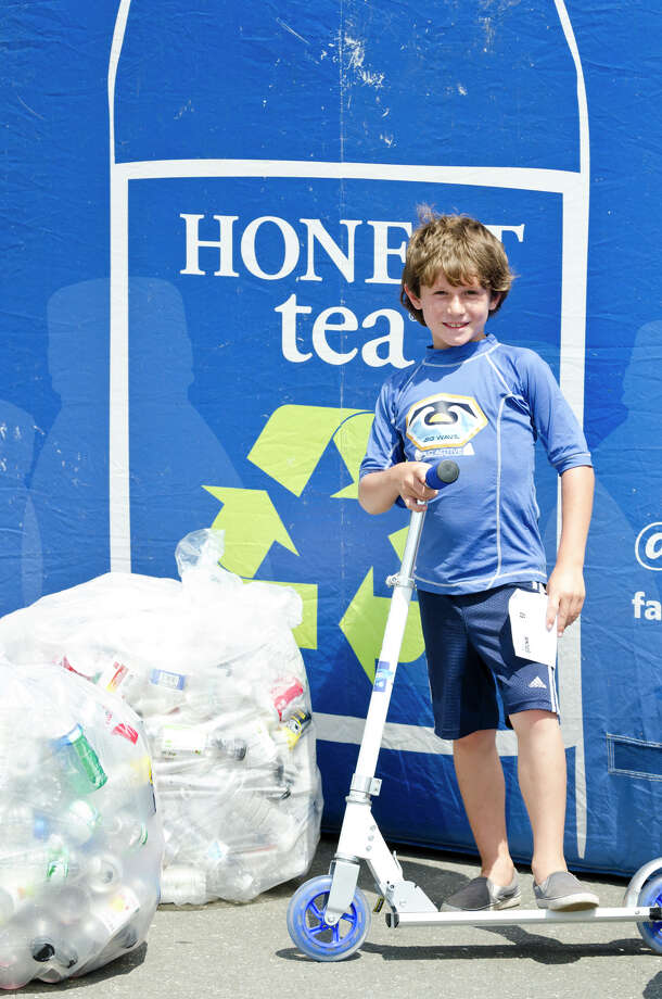 Daniel Folloni, 8, of Milford, displays the Razor scooter that he won from the Honest Tea booth for collecting 500 recyclable cans and bottles (pictured) during the 39th annual Milford Oyster Festival in downtown Milford on Saturday, Aug. 17, 2013. Photo: Amy Mortensen / Connecticut Post Freelance