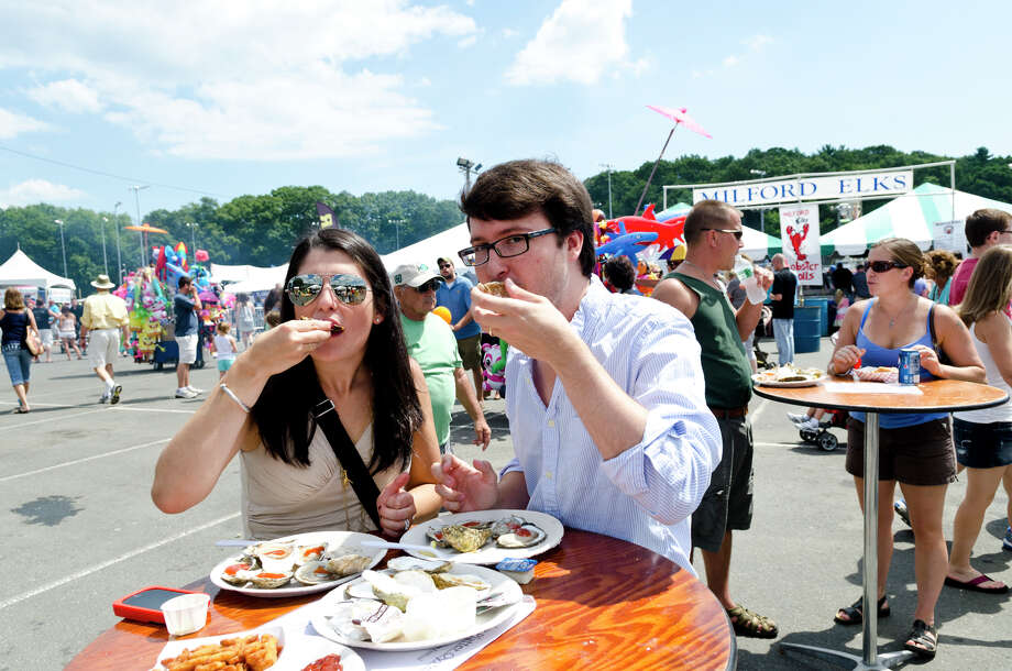 Caroline Walker and her husband, Marc, of New Haven, enjoy oysters during the 39th annual Milford Oyster Festival in downtown Milford on Saturday, Aug. 17, 2013. Photo: Amy Mortensen / Connecticut Post Freelance