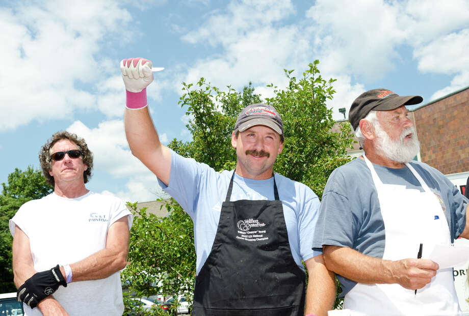 "Steve Trcka, of Milford, William ""Chopper"" Young, of Wellfleet, and Ed Rhodes, of the East Coast Shellfish Growers Association, during the first heat of the oyster shucking contest during the 39th annual Milford Oyster Festival in downtown Milford on Saturday, Aug. 17, 2013. Photo: Amy Mortensen / Connecticut Post Freelance"