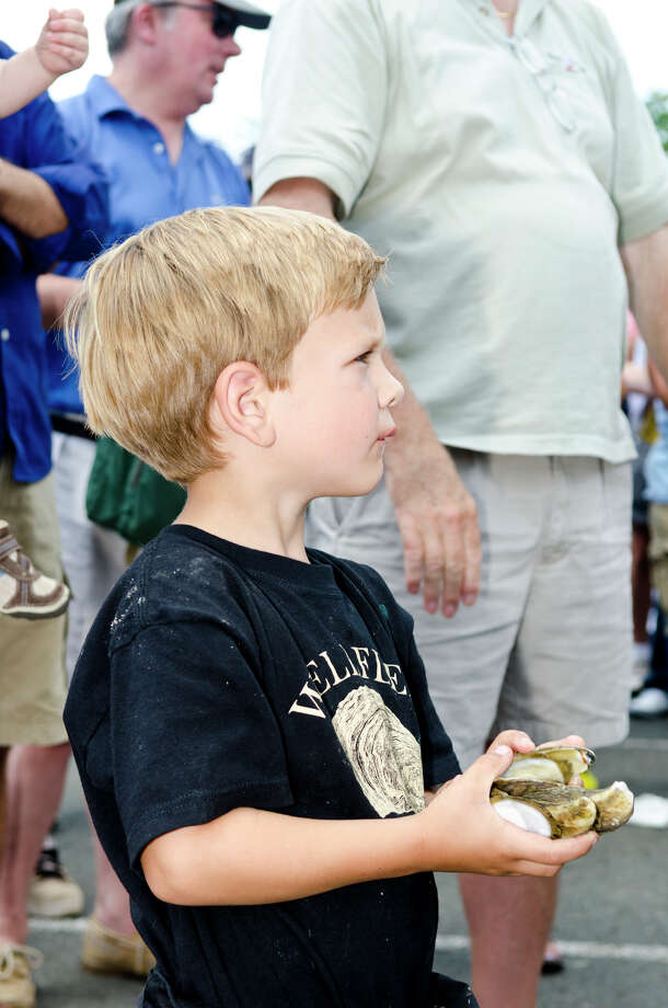 "Eli Paine, 4, of Wellfleet, holds discarded oyster shells as he watches his father, William ""Chopper"" Young compete in the oyster shucking contest during the 39th annual Milford Oyster Festival in downtown Milford on Saturday, Aug. 17, 2013. Photo: Amy Mortensen / Connecticut Post Freelance"