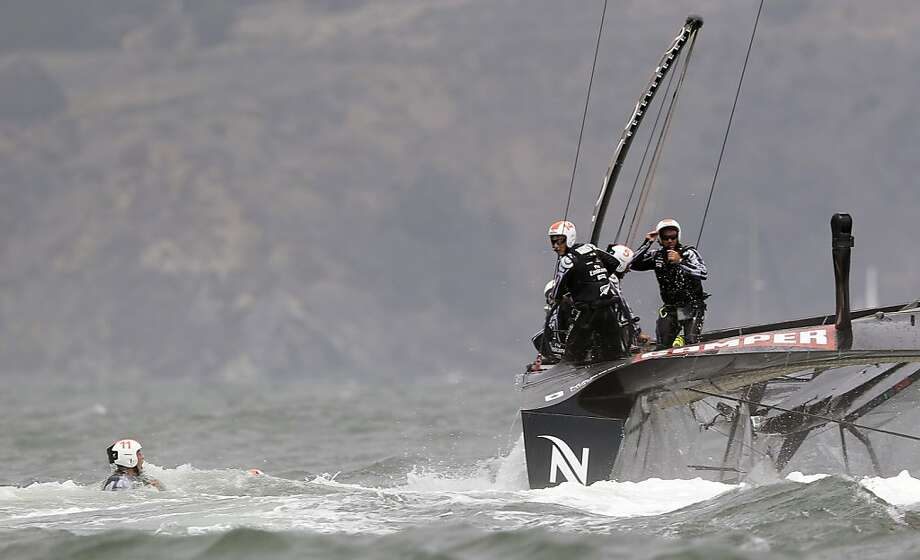 Skipper Dean Barker (14), of Emirates Team New Zealand, looks on as grinders Rob Waddell (11) and Chris Ward, center, float after after they fell during a sharp turn past the windward marks during the first race against Luna Rossa Challenge, of Italy, in their America's Cup challenger series final sailing event on Saturday, Aug. 17, 2013, in San Francisco. (AP Photo/Eric Risberg) Photo: Eric Risberg, Associated Press