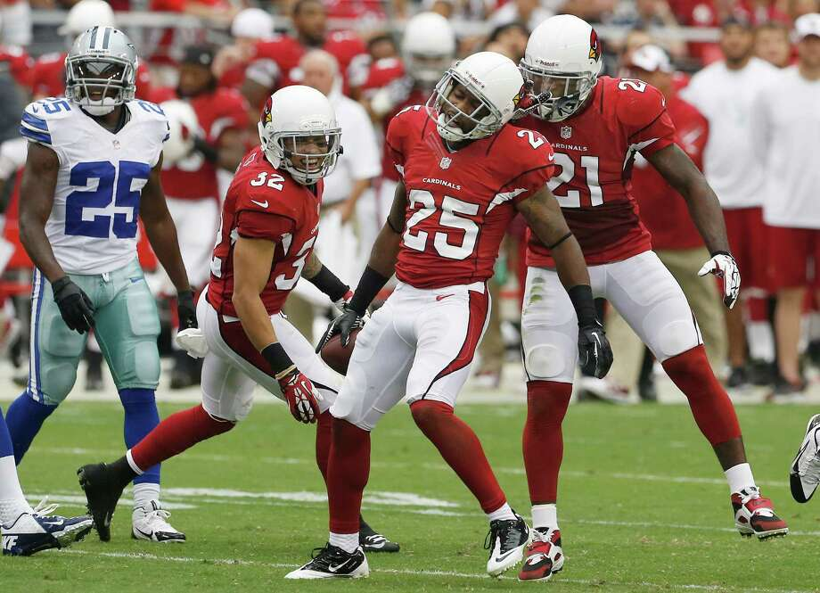 Arizona Cardinals' Jerraud Powers, decond from right, celebrates his interception with teammates Tyrann Mathieu (32) and Patrick Peterson (21) as Dallas Cowboys' Lance Dunbar, left, looks on in the first half during a preseason NFL football game on Saturday, Aug. 17, 2013, in Glendale, Ariz. (AP Photo/Ross D. Franklin) Photo: Ross D. Franklin, Associated Press / AP