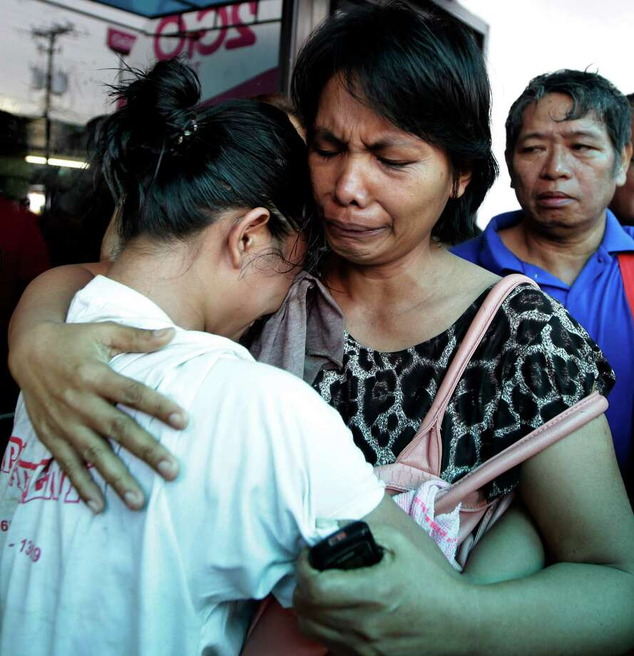 A survivor, left, of the ill-fated passenger ferry MV Thomas Aquinas, is comforted by a relative. Photo: Bullit Marquez, STF / AP