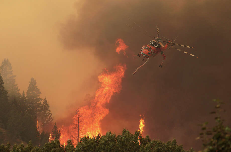 Helicopters battle the 64,000 acre Beaver Creek Fire on Friday, Aug., 16, 2013 north of Hailey, Idaho. A number of residential neighborhoods have been evacuated because of the blaze.(AP Photo/Times-News, Ashley Smith) MANDATORY CREDIT ORG XMIT: IDTWF102 Photo: Ashley Smith / The Times-News