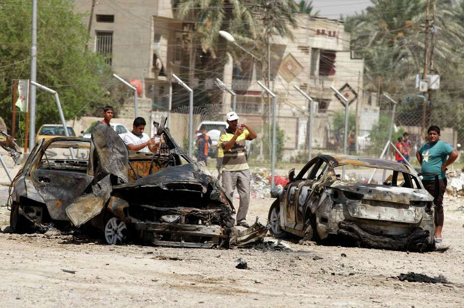 Civilians inspect the aftermath of a car bomb attack in Baghdad, Iraq, Thursday, Aug. 15, 2013. A wave of car bombs in the Iraqi capital on Wednesday killed 26 people and wounded dozens, the latest attacks in a months-long surge in violence. More than 3,000 people have been killed in violence during the past few months, raising fears Iraq could see a new round of widespread sectarian bloodshed similar to that which brought the country to the edge of civil war in 2006 and 2007. (AP Photo/Karim Kadim) ORG XMIT: BAGXKK110 Photo: Karim Kadim / AP