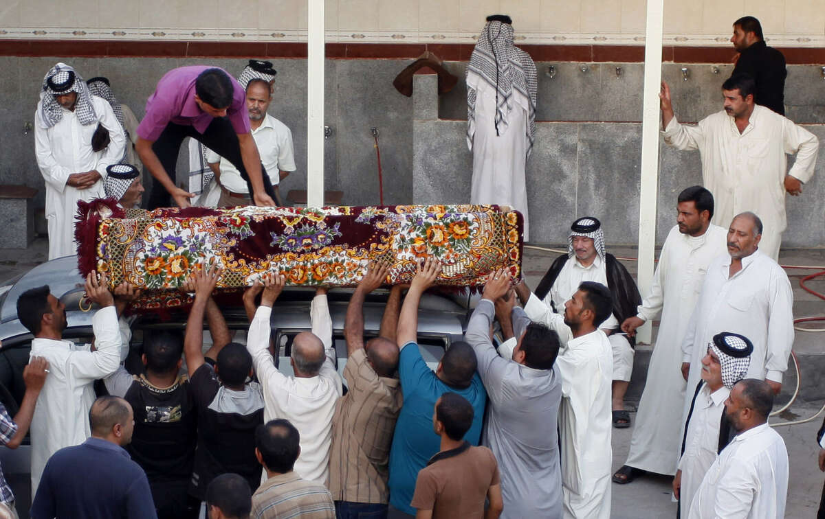 Mourners unload the coffin of a 22-year-old killed in a car-bomb attack in the Shiite holy city of Najaf, 100 miles south of Baghdad in Iraq.