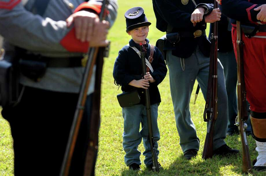 Hunter Brown, 6, of North Adams, Mass., a reenactor with the 123rd New York, grins for a picture as he stands at parade rest during Civil War Heritage Days on Saturday, Aug. 17, 2013, at Schuyler Flatts Cultural Park in Colonie, N.Y. The encampment continues Sunday from 10 a.m. to 4 p.m. (Cindy Schultz / Times Union) Photo: Cindy Schultz / 00023545A