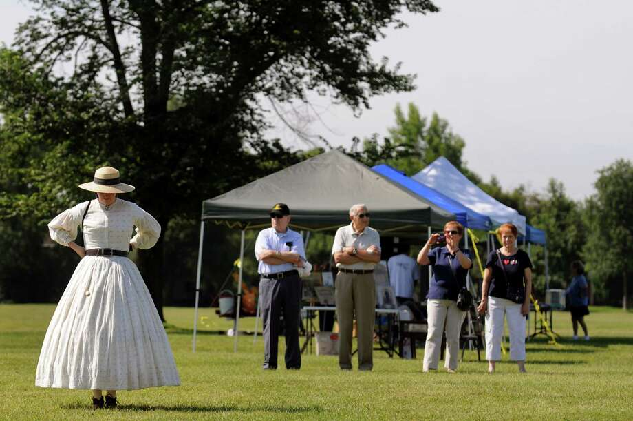 Jeannette Eckert of East Dover, Vt., a reenactor with the 123rd New York, left, joins festival goers during Civil War Heritage Days on Saturday, Aug. 17, 2013, at Schuyler Flatts Cultural Park in Colonie, N.Y. The encampment continues Sunday from 10 a.m. to 4 p.m. (Cindy Schultz / Times Union) Photo: Cindy Schultz / 00023545A