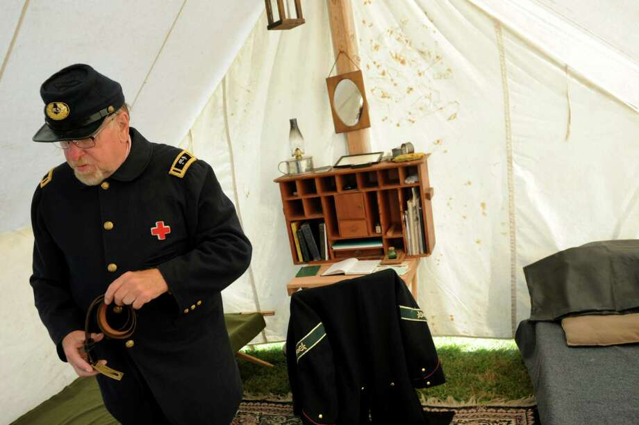 Carl Sahre of Herkimer, a reenactor portraying an assistant surgeon with the 121st New York, gets ready in the officer's tent during Civil War Heritage Days on Saturday, Aug. 17, 2013, at Schuyler Flatts Cultural Park in Colonie, N.Y. The encampment continues Sunday from 10 a.m. to 4 p.m. (Cindy Schultz / Times Union) Photo: Cindy Schultz / 00023545A