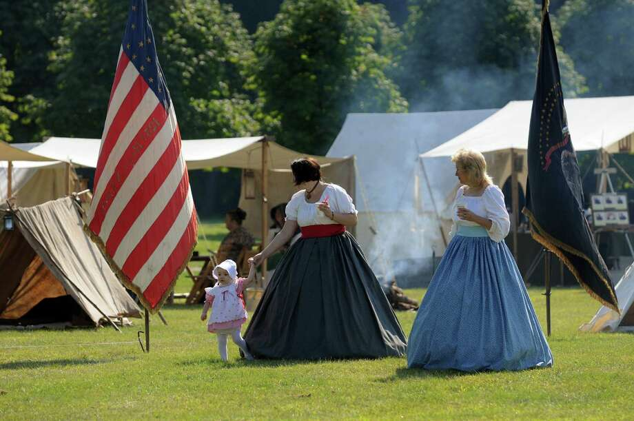 Reenactors Alyvia McEvilly, 15 months, left, her mother, Lauren, center, and friend Pat Verhagen, all of Watervliet, walk through the encampment during Civil War Heritage Days on Saturday, Aug. 17, 2013, at Schuyler Flatts Cultural Park in Colonie, N.Y. The encampment continues Sunday from 10 a.m. to 4 p.m. (Cindy Schultz / Times Union) Photo: Cindy Schultz / 00023545A