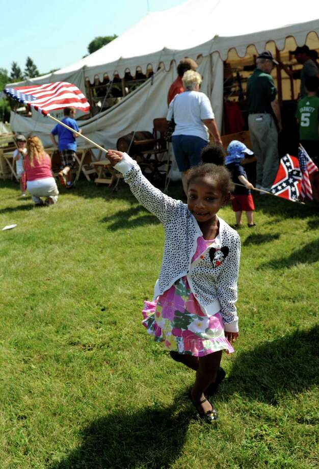 Mia Rogers, 4, of Albany twirls around with a flag during Civil War Heritage Days on Saturday, Aug. 17, 2013, at Schuyler Flatts Cultural Park in Colonie, N.Y. The encampment continues Sunday from 10 a.m. to 4 p.m. (Cindy Schultz / Times Union) Photo: Cindy Schultz / 00023545A