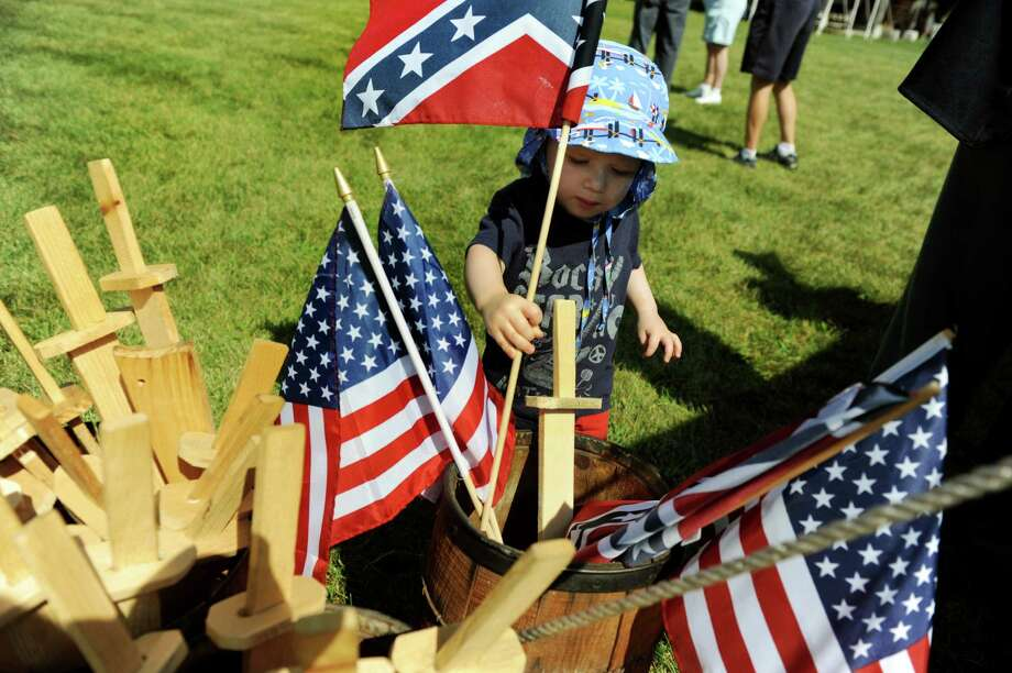 Camden Wantroba, 2, of Watervliet plays with the flags during Civil War Heritage Days on Saturday, Aug. 17, 2013, at Schuyler Flatts Cultural Park in Colonie, N.Y. The encampment continues Sunday from 10 a.m. to 4 p.m. (Cindy Schultz / Times Union) Photo: Cindy Schultz / 00023545A