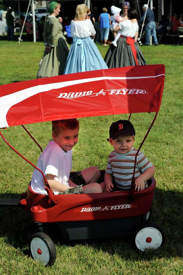Cameron Petersen, 8, of Cohoes, left, and his brother David Batchelor, 2, ride in a canopy-covered wagon during Civil War Heritage Days on Saturday, Aug. 17, 2013, at Schuyler Flatts Cultural Park in Colonie, N.Y. The encampment continues Sunday from 10 a.m. to 4 p.m. (Cindy Schultz / Times Union) Photo: Cindy Schultz / 00023545A