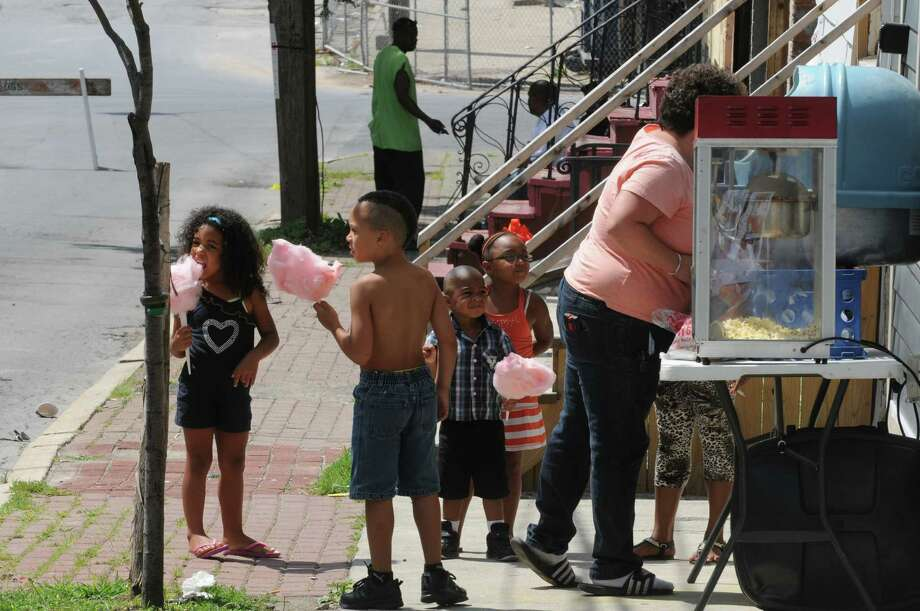 Children enjoy cotton candy during the 3rd Annual Remembering Fallen Stars block party sponsored by Sister to Sister Awakening,Inc. on Saturday Aug. 17, 2013 in Albany, N.Y. (Michael P. Farrell/Times Union) Photo: Michael P. Farrell / 00023318A