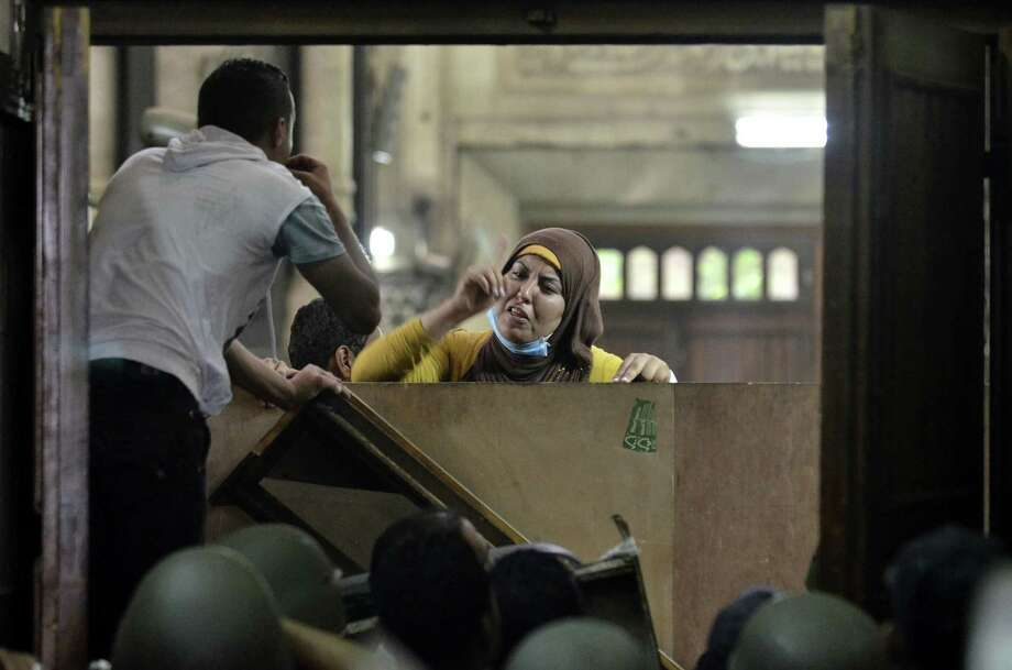 TOPSHOTS-An Egyptian woman talks to policemen from the inside of Cairo's Al-Fath mosque where Islamist supporters of ousted president Mohamed Morsi hole up on August 17, 2013. The standoff at al-Fath mosque in central Ramses Square began on August 16, with security forces surrounding the building where Islamists were sheltering and trying to convince them to leave.  AFP PHOTO / MOHAMED EL-SHAHEDMOHAMED EL-SHAHED/AFP/Getty Images Photo: MOHAMED EL-SHAHED / AFP