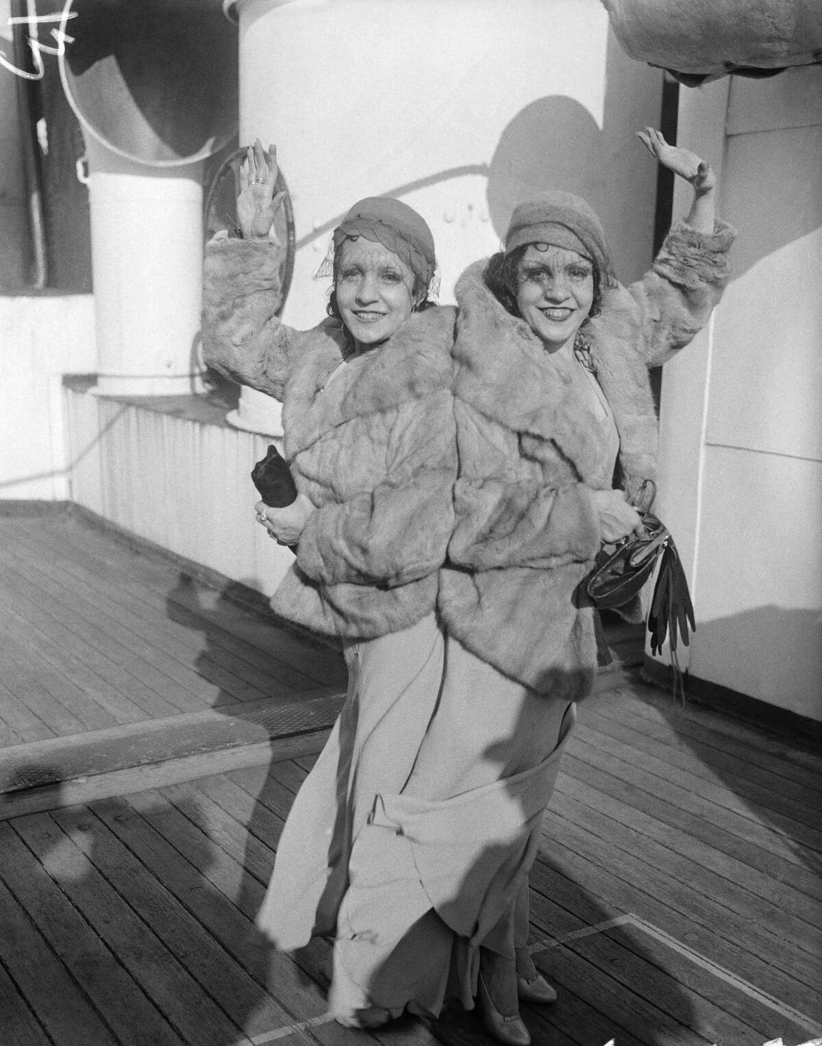 Violet and Daisy Hilton, conjoined twins, are pictured upon their arrival in New York, Oct. 6, 1933, aboard the Aquitania. Although they have been joined together since birth and cannot be separated, they say they are engaged and will have a double wedding within a year. Daisy claims to be engaged to Jack Lewis, an orchestra leader in Chicago and Violet reports that her fiancee is a prominent English boxer, but declined to reveal his name.