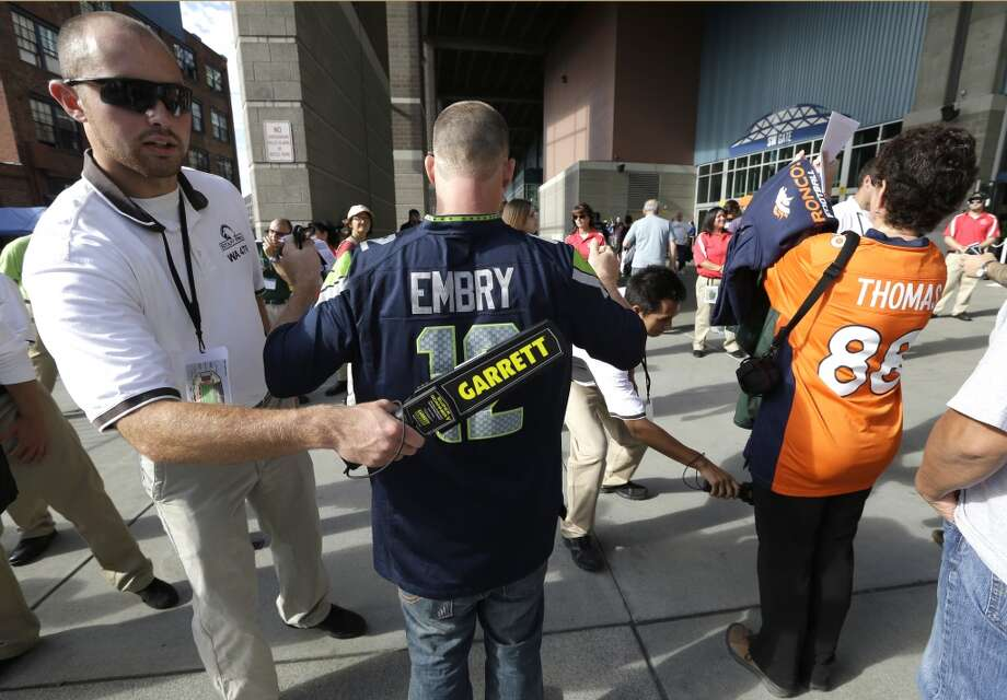Security screeners at CenturyLink Field check fans with a detector as they enter the stadium for a preseason NFL football game between the Seattle Seahawks and the Denver Broncos, Saturday, Aug. 17, 2013, in Seattle. (AP Photo/Elaine Thompson) Photo: AP