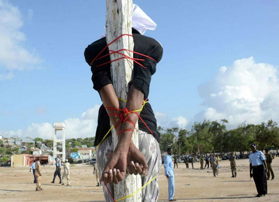 Somali convicted murderer Adan Sheikh Abdi is tied to a post before being executed Saturday by a firing squad in a Mogadishu square for the September 2012 killing of a well-known journalist. Photo: Mohamed Abdiwahab / Getty Images